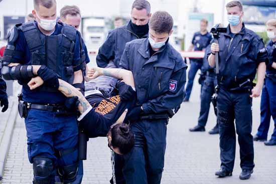 Ein Tierschutzaktivist wird von Polizisten bei einer Blockade des Schlachthofes von der Einfahrt zum Betriebsgelände weggetragen. Foto: Christoph Soeder/dpa